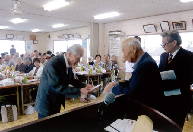 通山老人会長より80歳の記念品を受ける藤井修さん