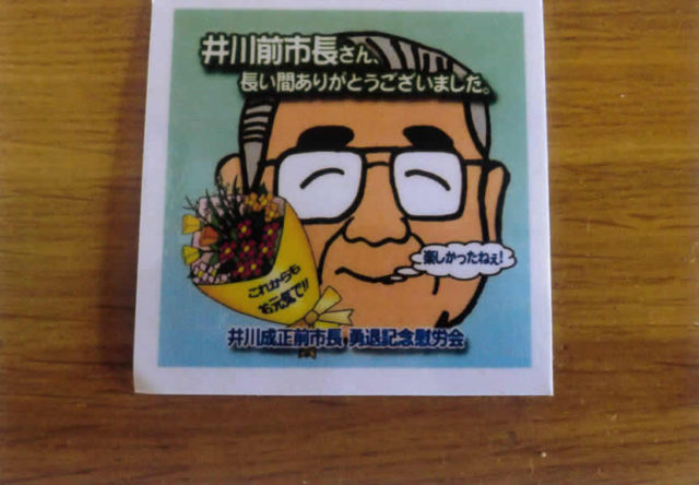 後援会が作った井川さんの笑顔のコースターが出席者にくばられた