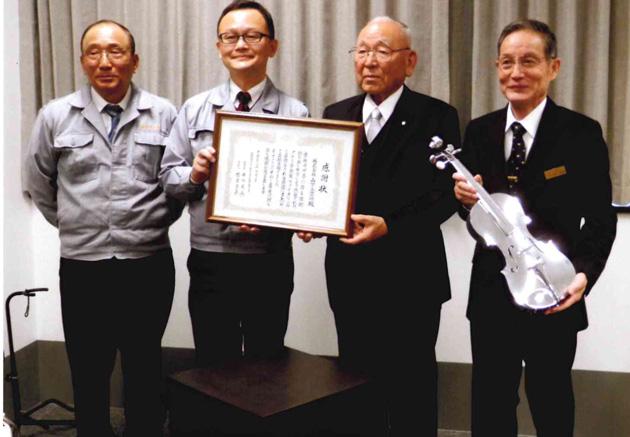 井川理事長から山下社長へ感謝状、寄贈されたバイオリンを持つ有吉支配人