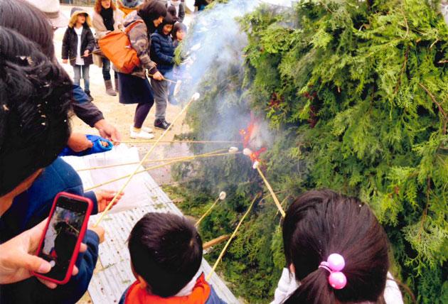 竹の先で小餅を焼く