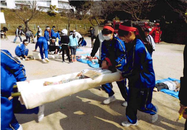 毛布と竹の臨時担架で運ぶ
