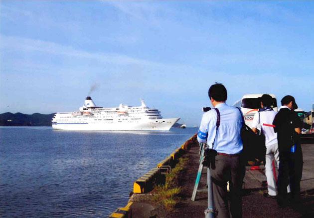 出航する船をカメラを持った人が追う